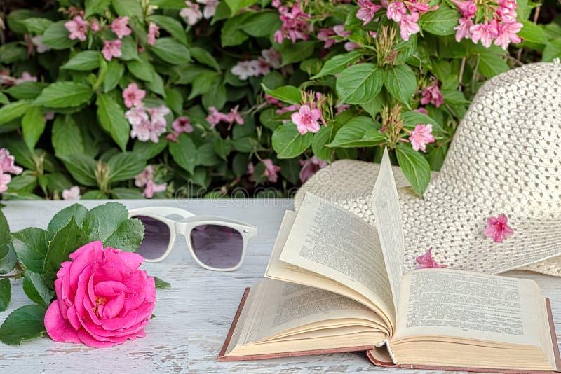Rosa del rosa, libro, sombrero en la tabla en el jardín, primer fotos de archivo libres de regalías