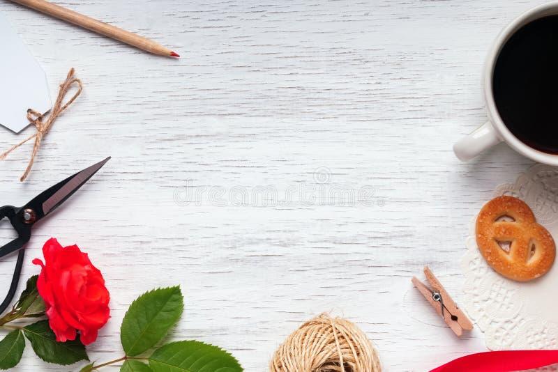 Rosa del rojo, café, tijeras y otros pequeños objetos en el blanco imagen de archivo