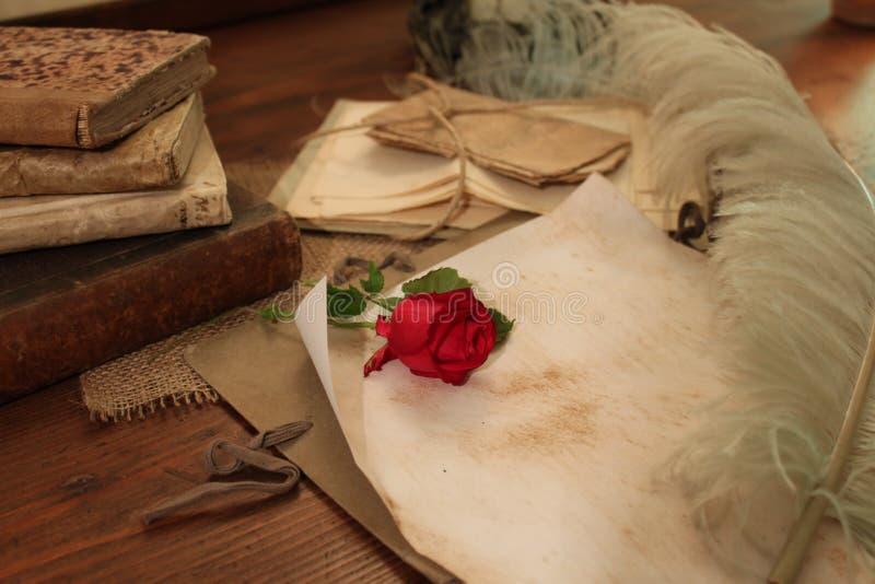 Rosa del rojo y canilla hermosa en un escritorio del vintage imagenes de archivo
