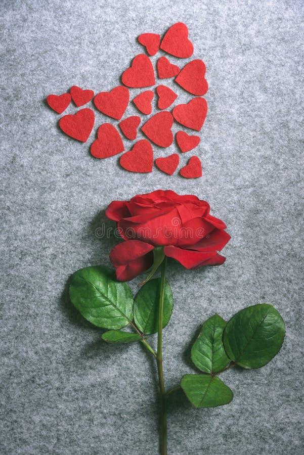 Rosa del rojo y un corazón de pequeños corazones rojos foto de archivo libre de regalías