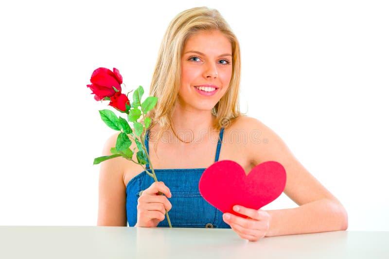 Rosa della holding della ragazza e cuore belli del biglietto di S. Valentino immagine stock