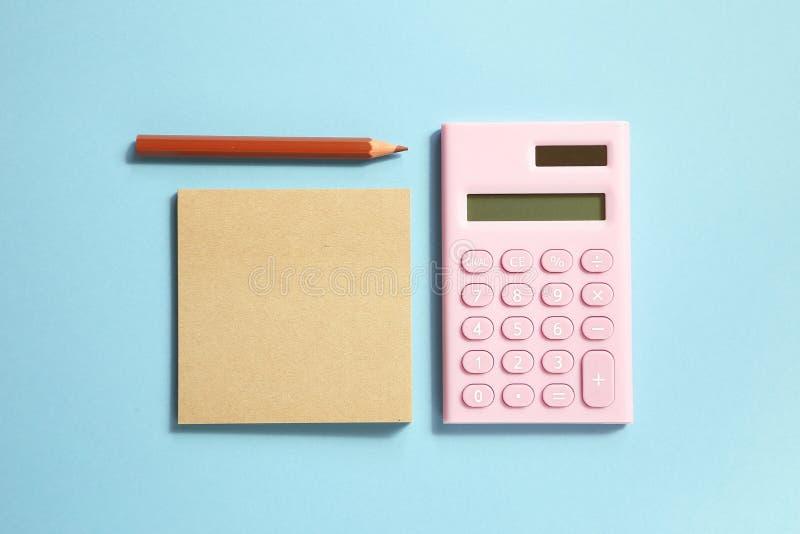 Rosa digital räknemaskin- och minneslistaanteckningsbok och brun kulör blyertspenna på blå bakgrund royaltyfri foto