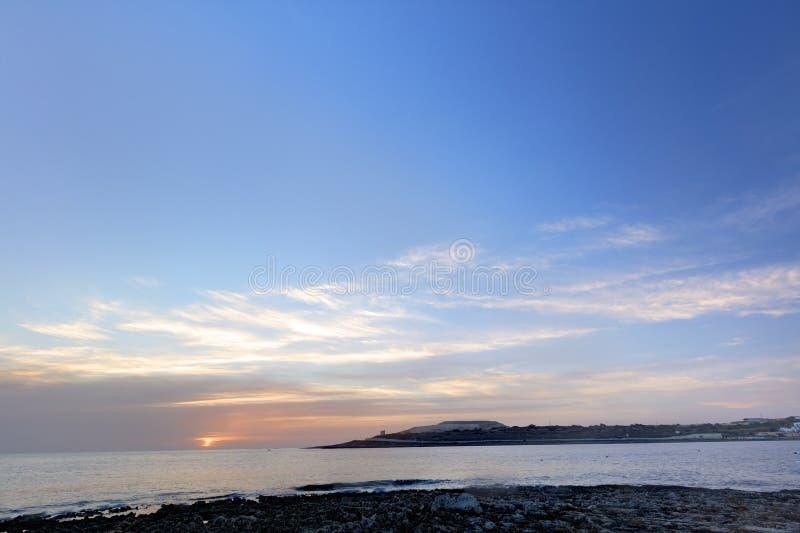 Rosa do nascer do sol no horizonte atrás do mar em Malta, St Paul fotos de stock royalty free