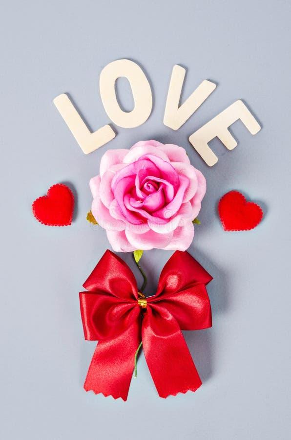 Rosa do rosa e palavra do amor com curva vermelha fotos de stock royalty free