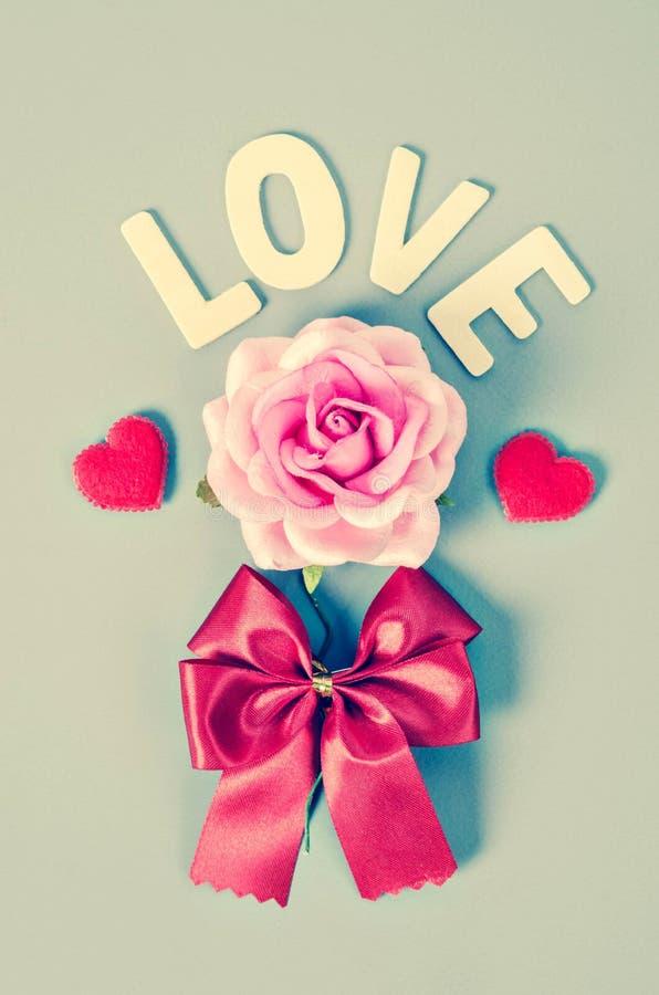 Rosa do rosa e palavra do amor com curva vermelha imagens de stock royalty free