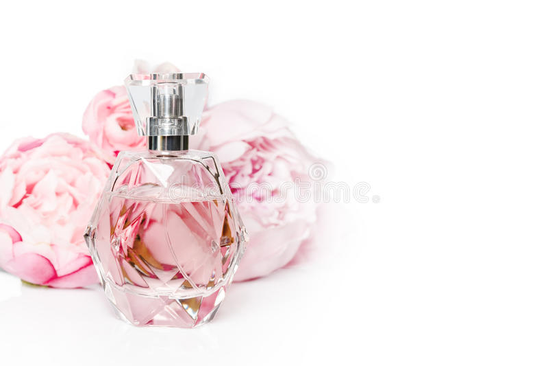 Rosa doftflaska med blommor på ljus bakgrund Parfymeriaffär skönhetsmedel, doftsamling arkivfoto