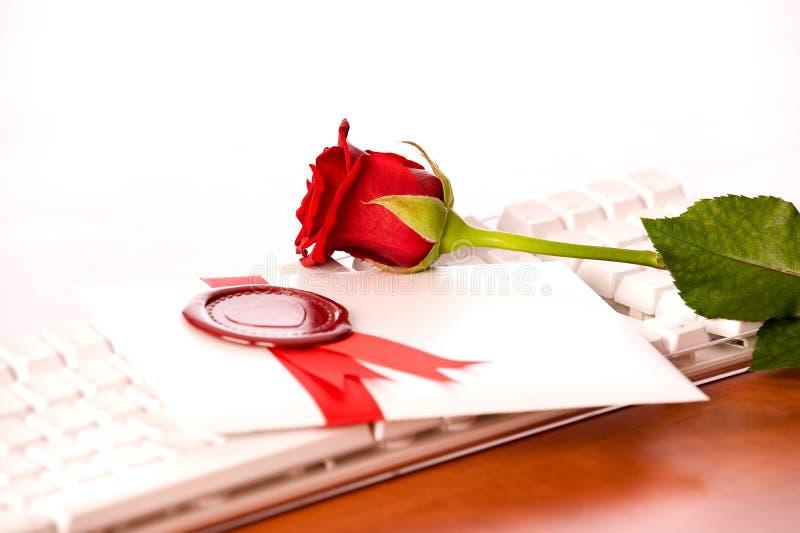 Rosa e amore-lettera sulla tastiera bianca fotografia stock