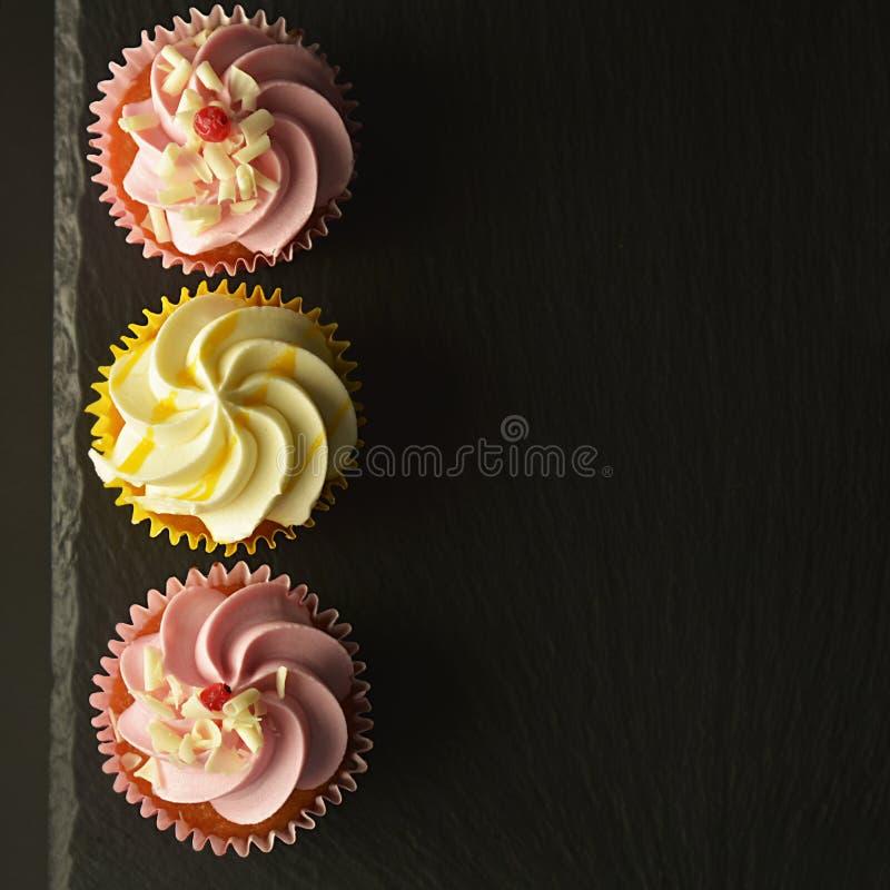 Rosa e bigné gialli contro i bigné di un fondo nero, di compleanno o del partito Alimento dolce del partito, dessert Copi lo spaz immagini stock