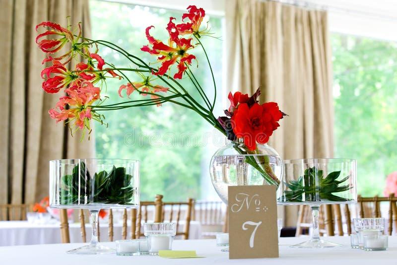 Rosa e mazzo rosso dei fiori dell'orchidea su una tavola in chiari barattoli di acqua durante la celebrazione di nozze fotografie stock libere da diritti