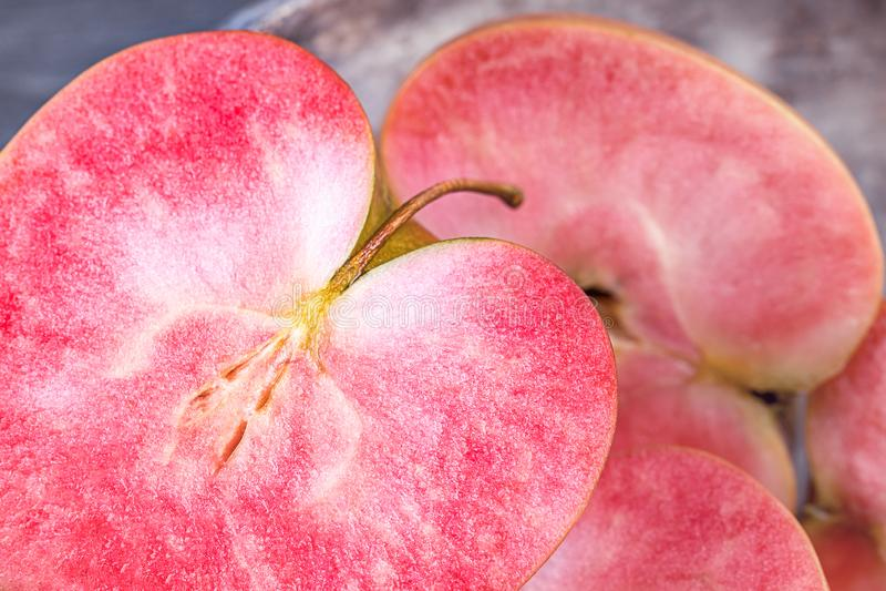 Rosa e mele fleshed rosse su un fondo scuro Mele con carne rosa immagini stock
