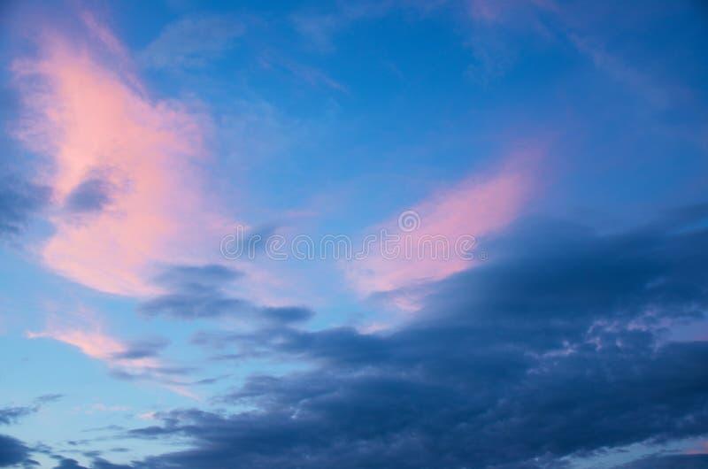 Rosa e nuvens azuis no céu do por do sol fotografia de stock royalty free