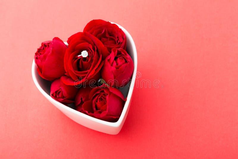 A rosa e o anel de diamante do vermelho dentro do coração dão forma à bacia fotografia de stock royalty free