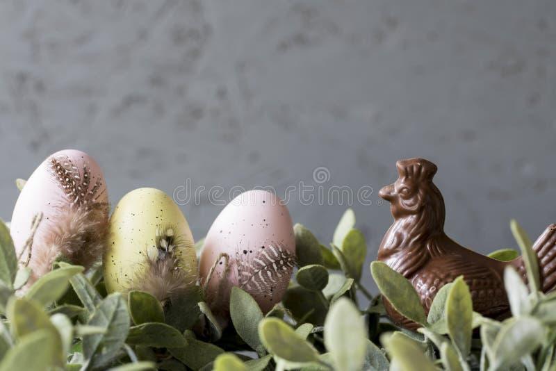 Rosa e ovos da páscoa amarelos nas folhas verdes, com galinha do chocolate, foto de stock royalty free