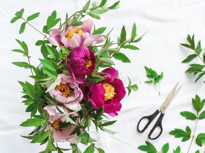 Rosa e peônias roxas em um vaso em uma tabela branca foto de stock royalty free