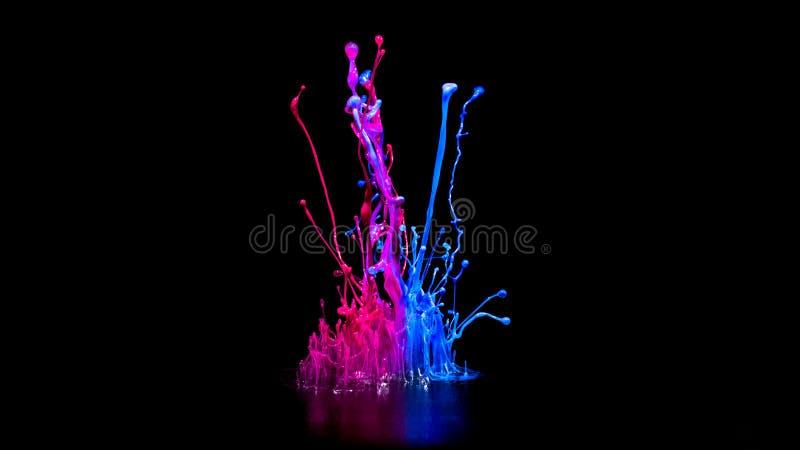 Rosa e pintura azul que espirram no orador audio isolado no fundo preto imagens de stock royalty free