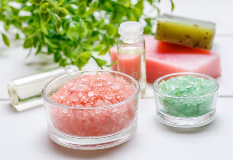 Rosa e sale marino verde in ciotole di vetro, in sapone fatto a mano, in due bottiglie con l'interno liquido e nel ramo della pia immagine stock libera da diritti
