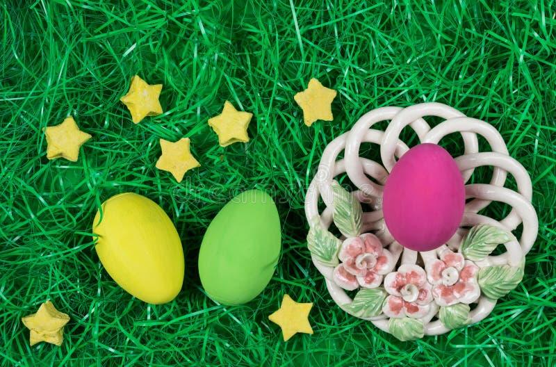 Rosa easter ägg i dekorativ bunke med blommor och gula och gröna ägg i grönt konstgjort gräs royaltyfria bilder