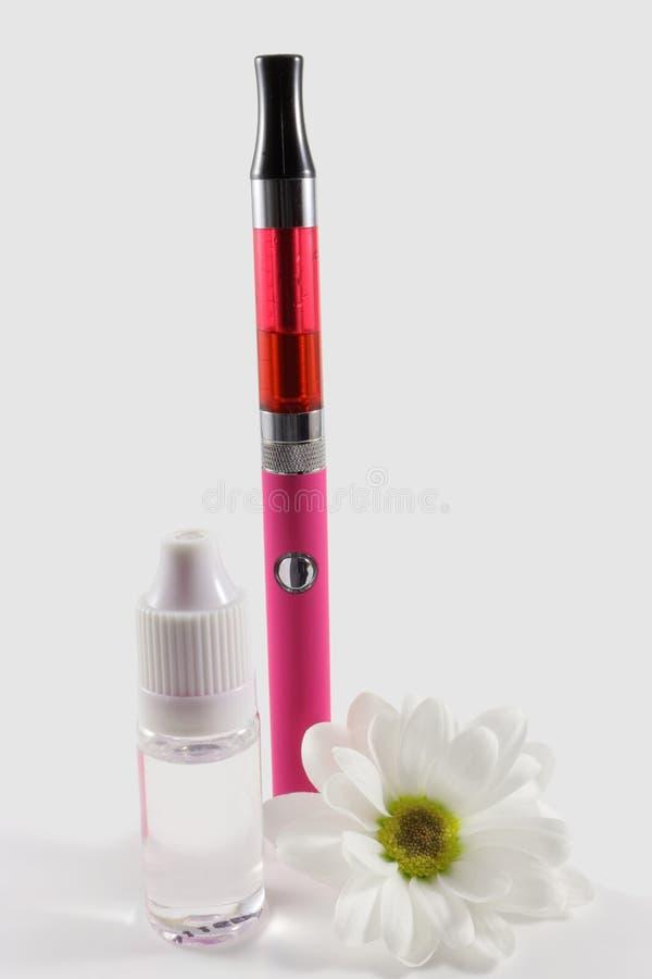 Rosa elektronisk cigarett och flaska av flytande som dekoreras med den vita blomman royaltyfri bild