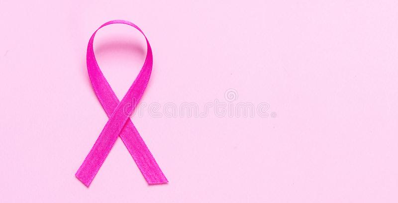 Rosa färgband mot pastellfärgad rosa bakgrund Bröstcancermedvetenhet arkivbilder
