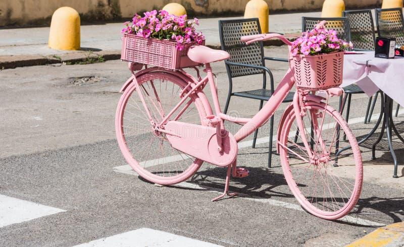 Rosa färgcykel med blommor som parkeras på gatan royaltyfria bilder