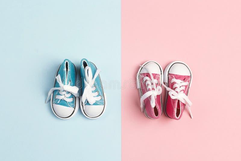 Rosa färger behandla som ett barn flicka- och för baby med hjärtfelpojken gymnastikskor på en rosa och blå bakgrund royaltyfri fotografi