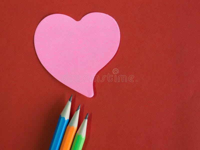 Rosa färger hjärta-formade anteckning på rött papper med färgrika blyertspennor royaltyfri bild