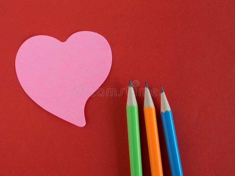 Rosa färger hjärta-formade anteckning på rött papper med färgrika blyertspennor royaltyfri fotografi