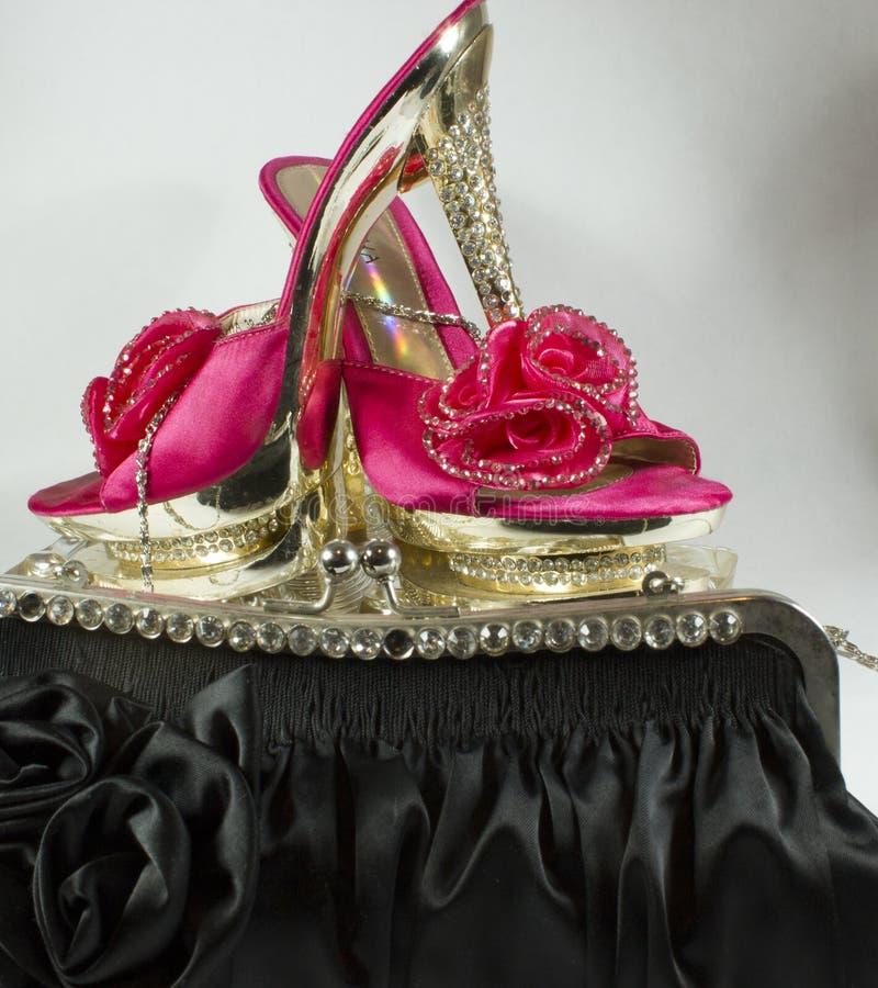 Rosa färger och guldskor, med blänker och blommar och svärtar påsen arkivfoto