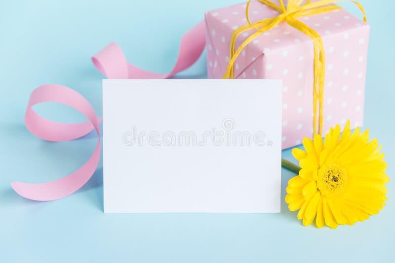 Rosa färger prucken gåvaask, gul gerberablomma och tomt kort över en blå bakgrund royaltyfria foton