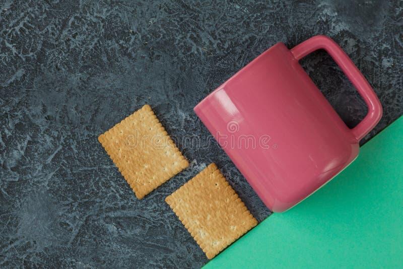 Rosa f?rger r?nar, och kakor p? m?rker stenar bakgrunds- och tegelplattapapper med kopieringsutrymme arkivfoto