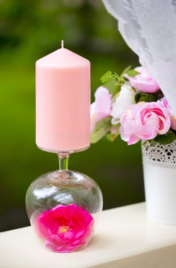 Rosa färger undersöker i grässtearinljushållare med den karmosinröda blomman arkivbilder