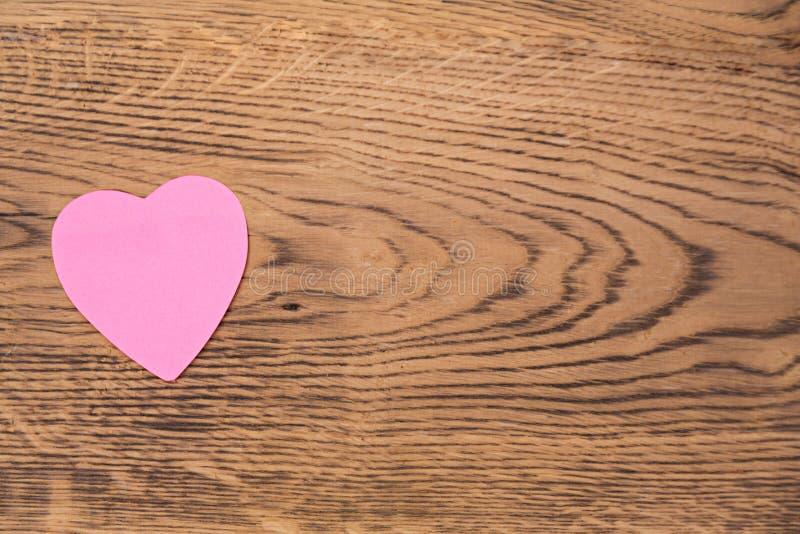 Rosa färghjärta stolpe-honom på en träbakgrund ?vers?ttning: ??lskar jag dig ?, royaltyfri bild
