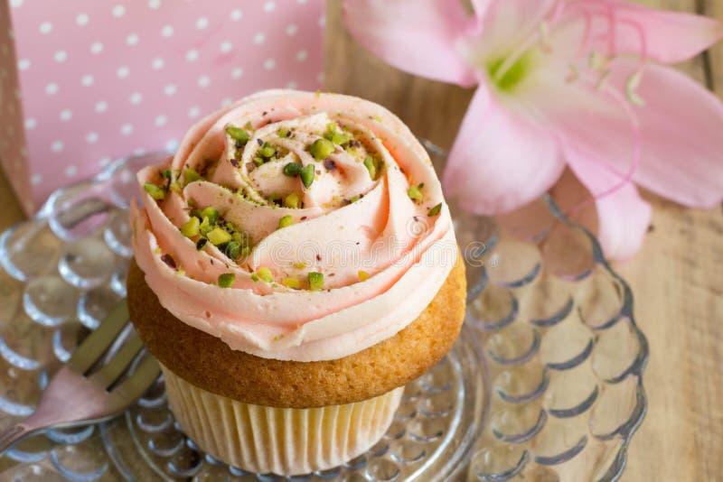 Rosa färgkoppkakan med gåvaasken och rosa färgliljan blommar för födelsedagce royaltyfri bild