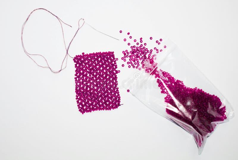 Rosa färgpärlor i en packe och en visare royaltyfri fotografi