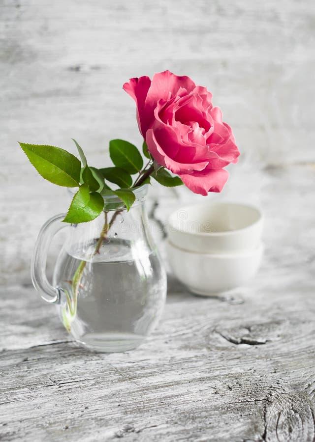 Rosa färgros i en glass vas på en vit yttersida arkivfoto
