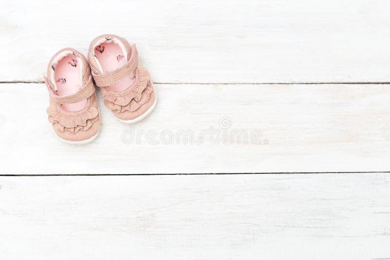 Rosa färgskor för liten flicka på en vit träbakgrund Kopieringssp royaltyfri foto