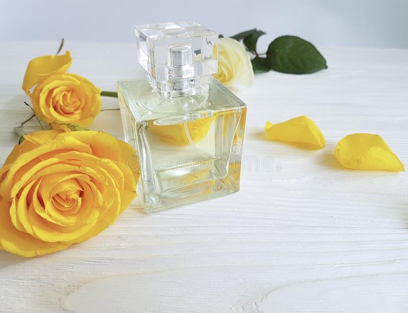 Rosa femminile di giallo del prodotto della bottiglia di profumo su un di legno immagine stock