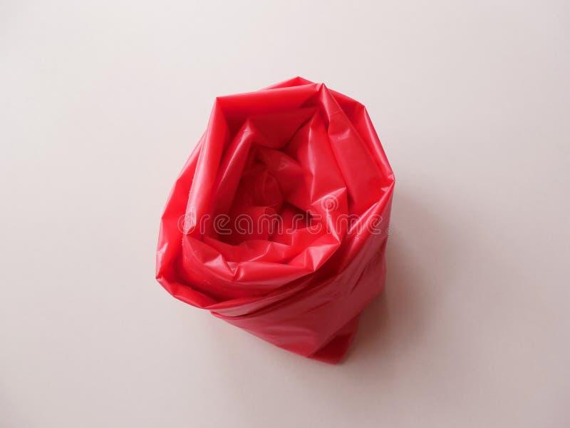 Rosa fez do saco de plástico vermelho fotografia de stock