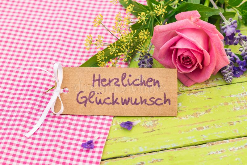 Rosa fiorisce il mazzo con la cartolina d'auguri ed il testo tedesco, Herzlichen Glueckwunsch, congratulazione di mezzi fotografia stock