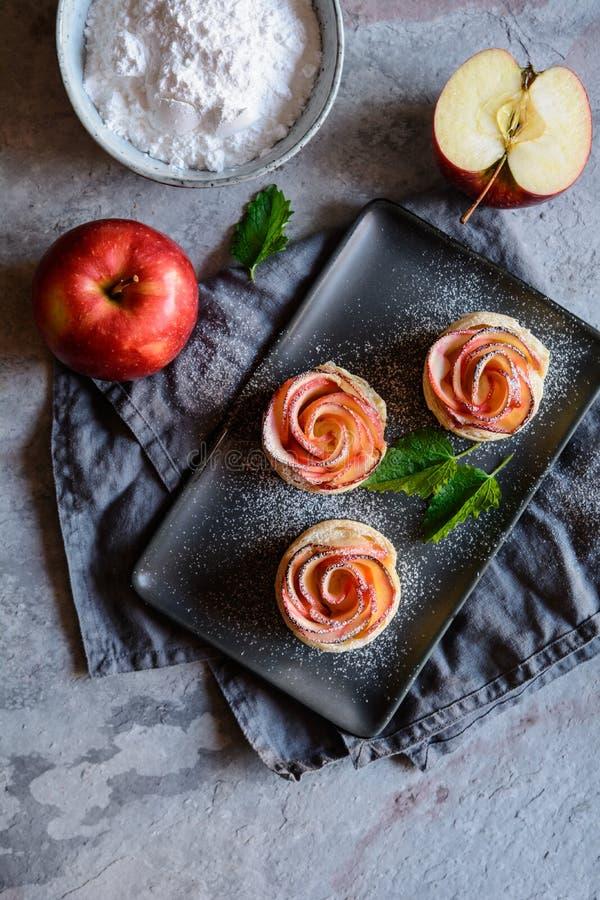 Rosa formade äppelpajer med damningen för pudrat socker royaltyfri fotografi