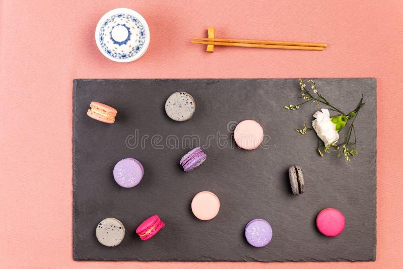 Rosa francés, macarrones púrpuras y magentas, flor blanca de la encarnación en una pizarra, palillos y cuenco de la porcelana en  imágenes de archivo libres de regalías