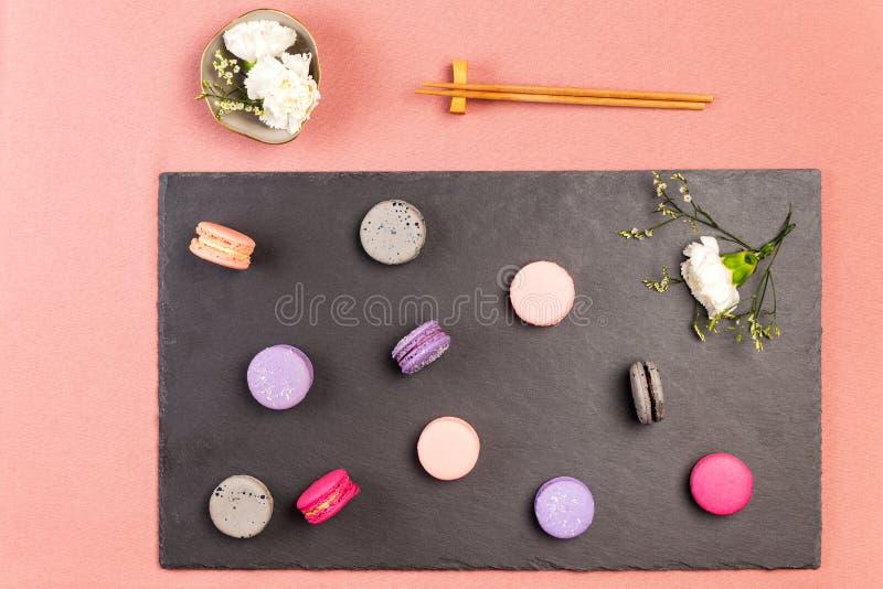 Rosa francés y macarons o macarrones magentas, y flor blanca de la encarnación en una pizarra, palillos y flores blancas de las e foto de archivo libre de regalías