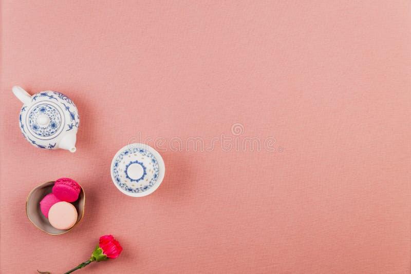 Rosa französische Makronen, in einer Schüssel mit pinkfarbener Inkarnationsblume und Chinawareteekanne und -schüssel über einem r stockbild