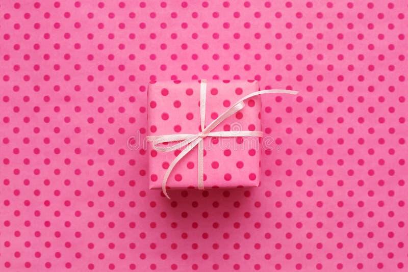 Rosa gåvaask på rosa bakgrund med prickar royaltyfri fotografi