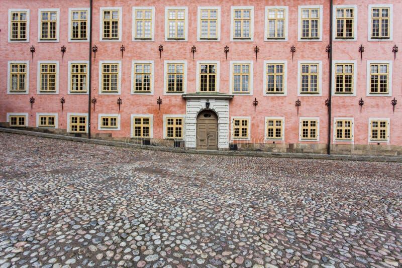Rosa Gebäude und cobblestoned Straße stockfotografie