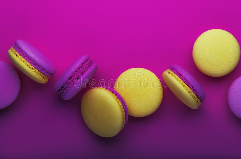 Rosa gelbe Makronen auf weicher rosa Hintergrundtabelle, Platz für Text, Minimalismusart, violette purpurrote Neonfarbe, Draufsic stockfotografie