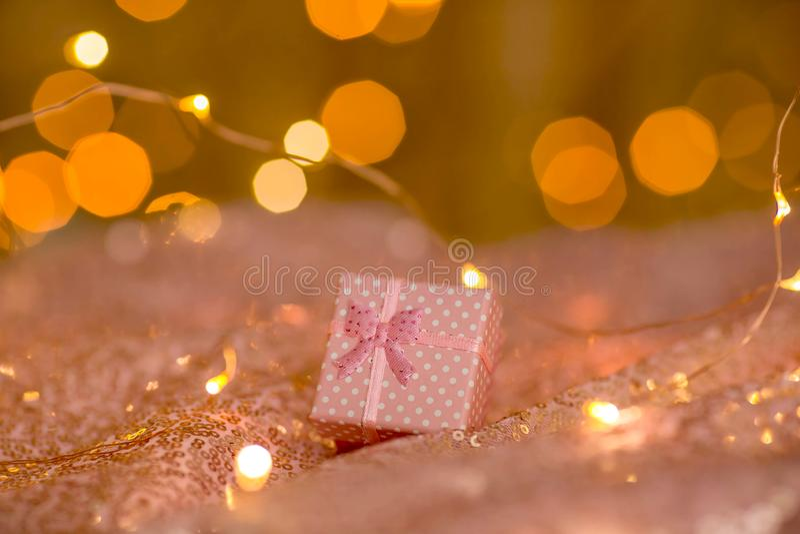 Rosa Geschenk auf einem korallenroten Hintergrund mit unscharfen Lichtern einer Girlande stockfotografie