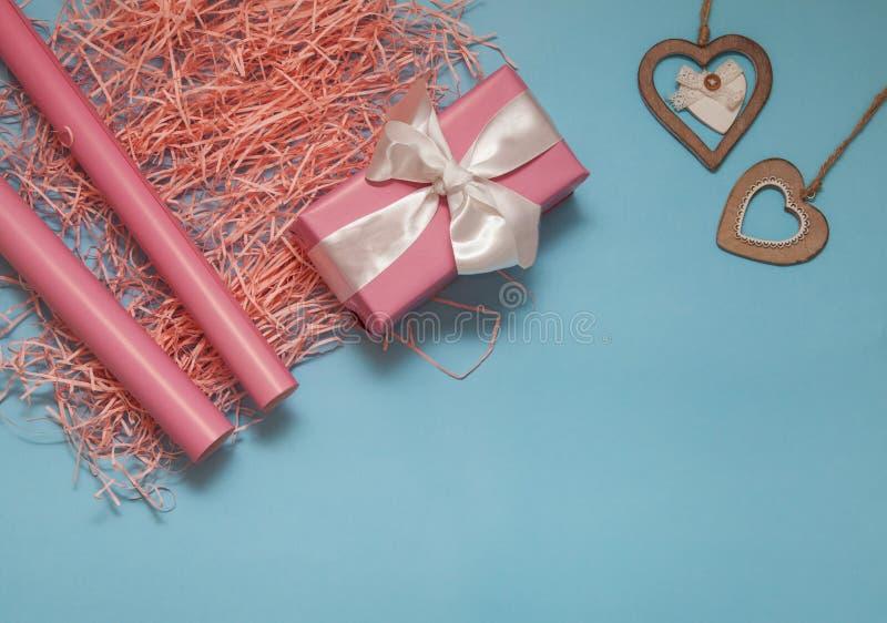 Rosa Geschenk mit Satinbogen, hölzernen Herzen, korallenroten Papierkonfettis und rosa Papier rools auf blauem Hintergrund Weihna lizenzfreie stockbilder