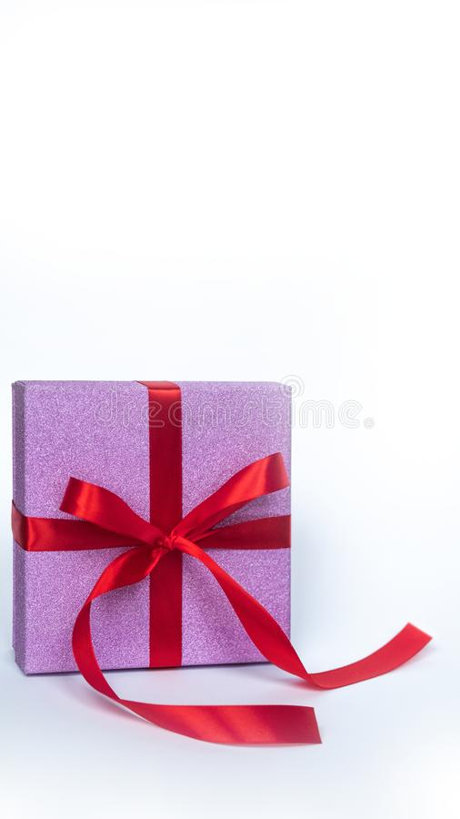 Rosa Geschenkbox mit rotem Band auf weißem Hintergrund Kopieren Sie Platz Getrennt stockbild