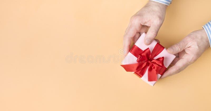 Rosa Geschenkbox mit rotem Bogen in männlichen Händen auf pastellfarbenem Untergrund Oberansicht Leerzeichen kopieren stockfoto